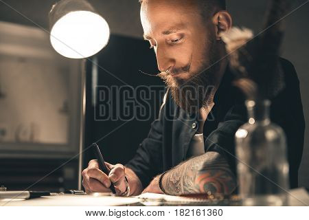 Low angle attentive bearded male artist drawing pictures. He sitting at table