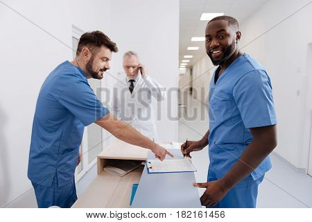 Signing everyday report. Smiling qualified upbeat practitioners working in the clinic and signing statement while senior colleague talking on the phone in the background