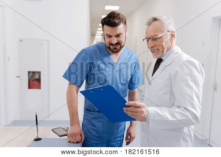 Interested in your opinion. Optimistic skillful old pediatrician working in the hospital and signing statement while senior colleague talking on the phone in the background