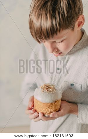 Small cute boy carefully holds in his hand an ornate Easter cake