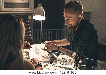 woman and side view calm male artists discussing tattoo image in apartment. He holding it in arms. They sitting at table