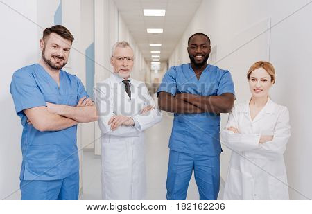 Sharing positivity. Cheerful skilled upbeat practitioners working in the hospital and standing with crossed arms while expressing positivity