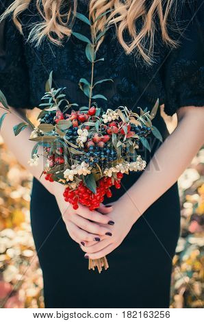 Bouquet of red black and white berries in the hands of a girl in a black dress. Beautiful young girl in a black dress with a bright bouquet of berries in hands. Autumn bouquet
