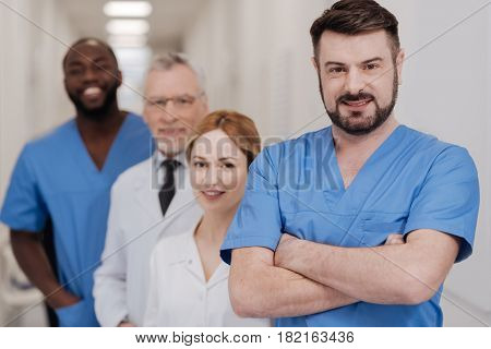 Proud of my international team. Handsome confident proficient practitioner enjoying responsibilities in the hospital and standing with crossed arms while smiling