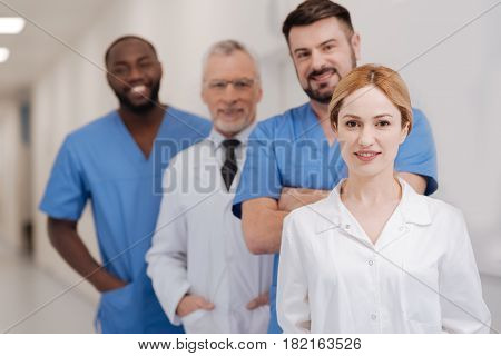 Career leader in medicine . Young cheerful charming nurse enjoying responsibilities at work and standing in the hospital while colleagues standing in the background