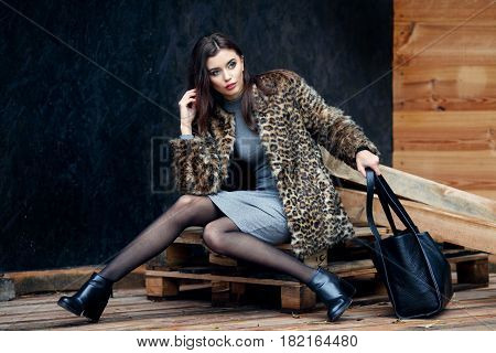 Fashion beautiful woman in a stylish fur coat and black boots with bag near a wooden wall