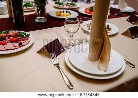 Beige napkin on a white empty plate next to blank guest card on a dining table. Table setting. Table served for wedding banquet close up view