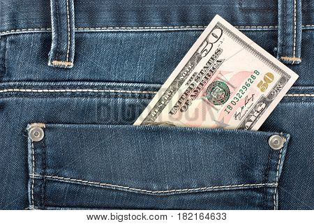 Fifty dollar note in the back pocket of denim trousers