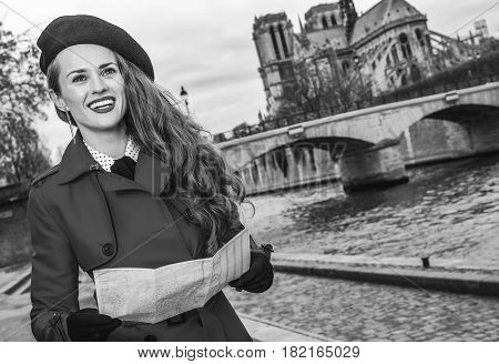Tourist Woman With Map In Paris Looking Into The Distance