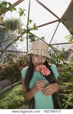 Native american teenager smelling flower in conservatory
