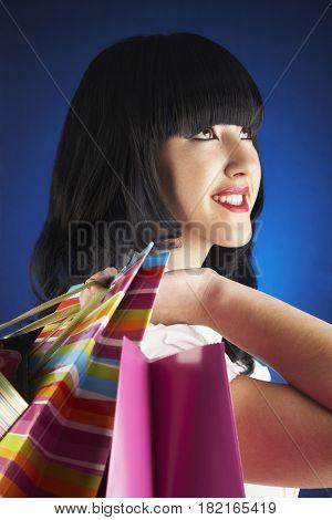 Glamorous Hispanic woman holding shopping bags