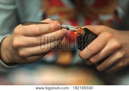 Vape After-sales Service Of The E-cigarette. Male Hands Regulate Electronic Cigarette Coils With Pin