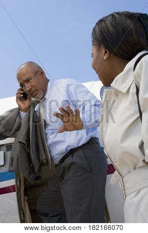 Hispanic businessman exiting jet while talking on cell phone