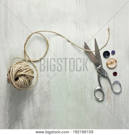 A square photo of vintage scissors with a roll of twine and buttons, shot from above on light wooden boards background texture, with copy space