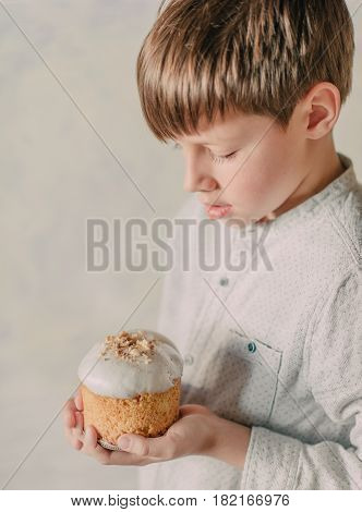 Small, cute boy carefully holds in his hand an ornate Easter cake