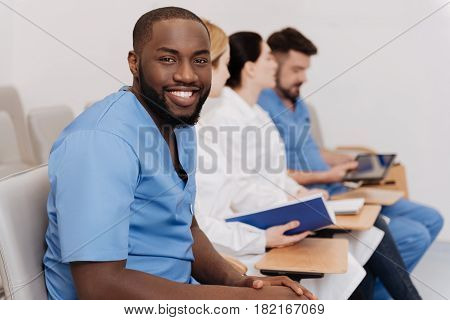 Preparing for future profession. Smiling diligent optimistic interns studying and listening the lecture in the medical college while expressing interest and taking notes