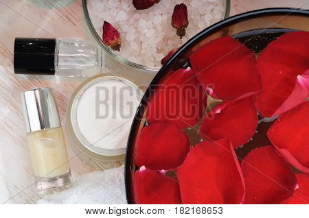 Accessories for manicure: hand bath with rose petals, essentials oils,  bath salt, towels, cream, nail polish. Beauty and spa concept