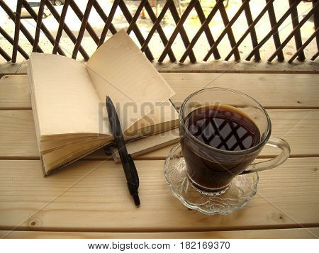 Cup of coffe and notebook with a pen on a wooden table on the veranda.