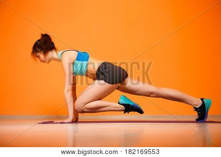 Young sport woman doing exercises on rug
