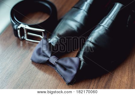 wedding accessories, black bow tie lies before leather shoes and belt. Grooms wedding morning