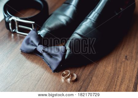 wedding accessories, black bow tie lies before leather shoes and belt. Grooms wedding morning. Wedding rings
