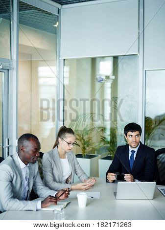 International group of modern young business people sitting at meeting table in conference room of modern office listening to discussion, African-American businessman among them