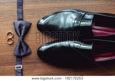 wedding accessories, black bow tie lies before leather shoes and belt. Grooms wedding morning. Wedding rings. Look from above