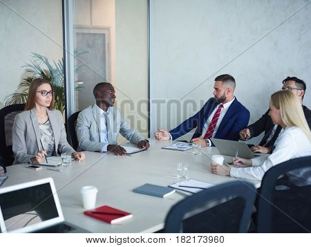 CEO board of directors meeting in conference room: multi ethnic group of business people discussing corporate issues, African-American man among them