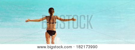 Happy bikini beach vacation woman running to ocean splashing water with open arms in freedom. Happiness carefree lifestyle banner with blue copyspace.