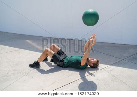 Strength training fit man cross training throwing medicine ball in the air for bench press arm workout exercises using heavy weight ball. Fitness athlete exercising on gym floor.