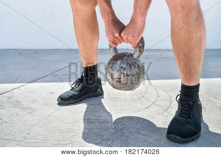 Fitness man cross training lifting kettlebell weight. Closeup of hands holding heavy weights for deadlift or squat workout exercise. Weightlifting concept.