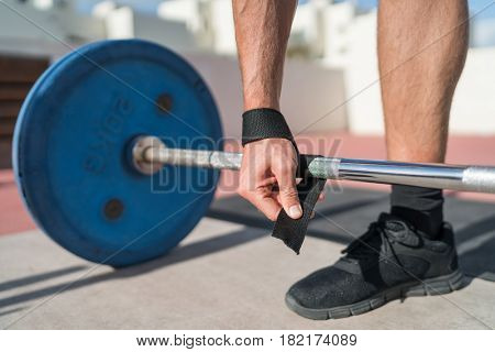 Weightlifting wrist straps support for bodybuilding and powerlifting. Fitness man wearing accessory during barbell weight workout at gym. Closeup of hand and bar.