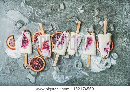 Healthy summer dessert. Blood orange, yogurt and granola popsicles on ice cubes over grey concrete background, top view, horizontal composition. Clean eating, dieting, weight loss concept