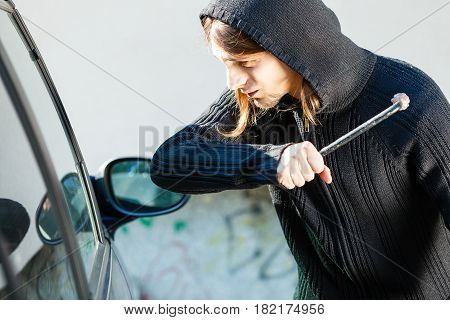 Transportation crime and ownership concept - Male hooded thief burglar breaking smashing the car window.