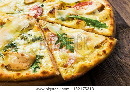 Delicious pizza with chicken, parmesan, tomatoes, white sauce and fresh arugula - thin pastry crust at wooden background, piece cut off