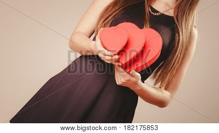 Valentine day. Woman in black holding three hearts boxes gifts presents. Part body of elegant model with valentines symbol sign. Studio shot.