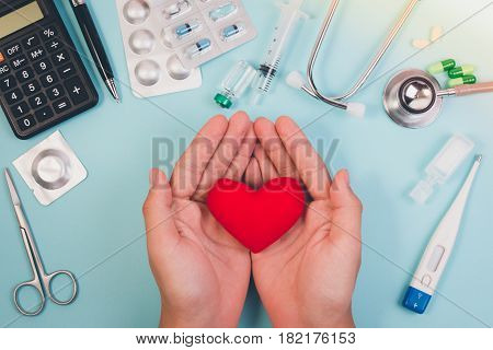 Topview Of Hands Holding Red Heart For Health Care Concept With Pen, Medicine, Calculator, Syringe,