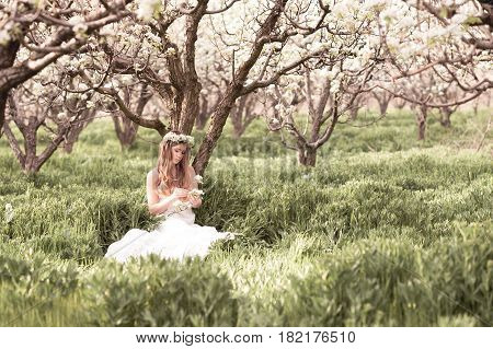 Beautiful teenage girl 14-16 year old resting in pear orchard sitting under tree outdoors. Holding flowers. Wearing stylish white dress.