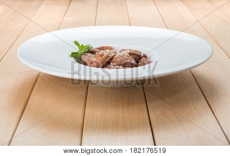 Traditional italian cuisine: red beetroot ravioli with blue cheese filling, sweet sauce and parmesan decorated with mint on white round plate on wood - diet and healthy food