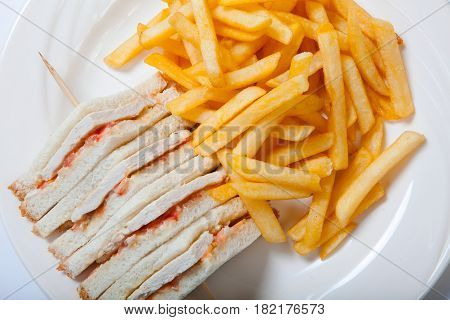 Different Types Of Sandwiches With French Fries On A White Plate