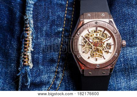 Automatic men watch with visible mechanism on blue jeans background.Skeleton men watch.