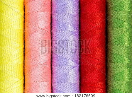 Close up colorful thread spools used in fabric and textile industry