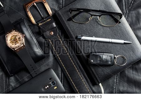 Men's accessories with wallet belt pen car keys glasses smartphone agenda and watch on black leather background.