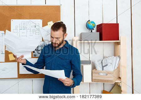 Young successful architector looking at  drawings, standing in office.