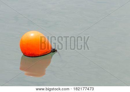 Close up one of orange sea buoys floating on sea background.