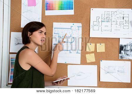 Young beautiful businesswoman pointing pencil at drawing, standing near desk in office.
