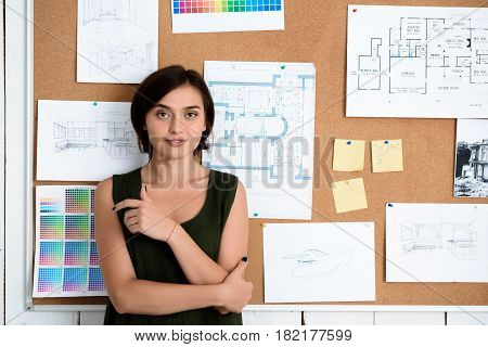 Young beautiful businesswoman smiling, standing near desk with drawings.