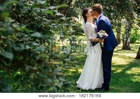 The bride and groom embracing and kissing. Bride and groom kissing. Wedding couple in love at wedding day