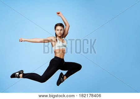 Nice girl in cool sportswear jumping high with hands up over blue background.