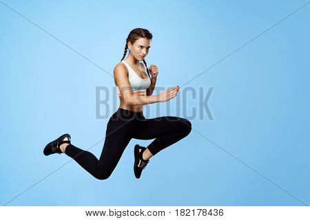 Nice motivated fitness girl in cool stylish sportswear jumping high with hands up looking away over blue background